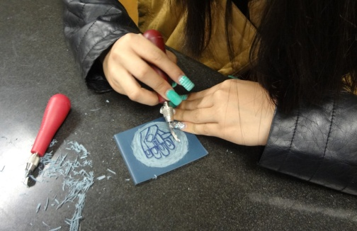The process of carving into linoleum.