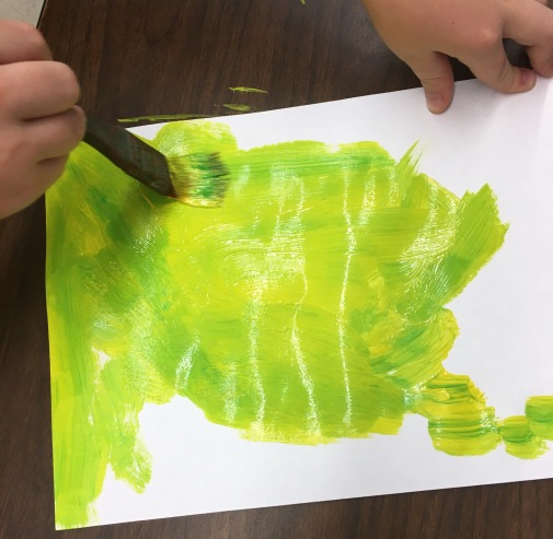 Art students create painted paper to use for their monarch collage.
